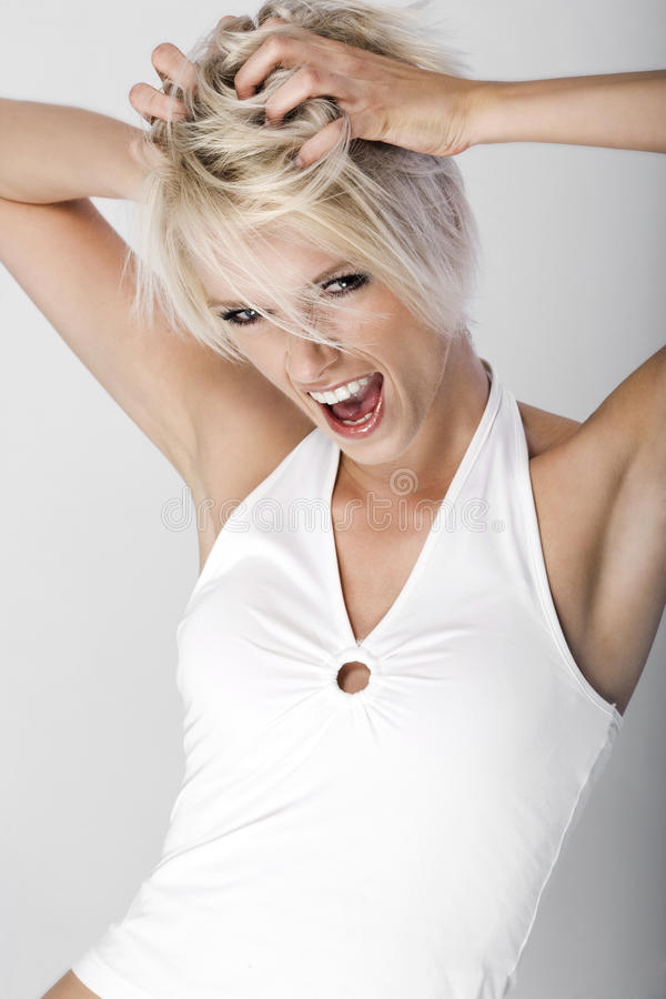Young woman throwing a tantrum or having a rave. Attractive young woman throwing a tantrum or having a rave standing shouting with her hands raised to her stock photo