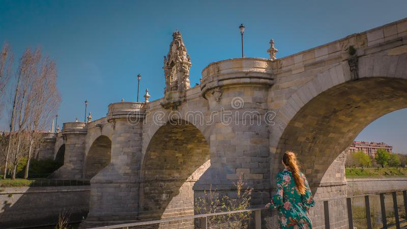 A young woman at Toledo medieval bridge at Madrid Rio park in Spain stock image