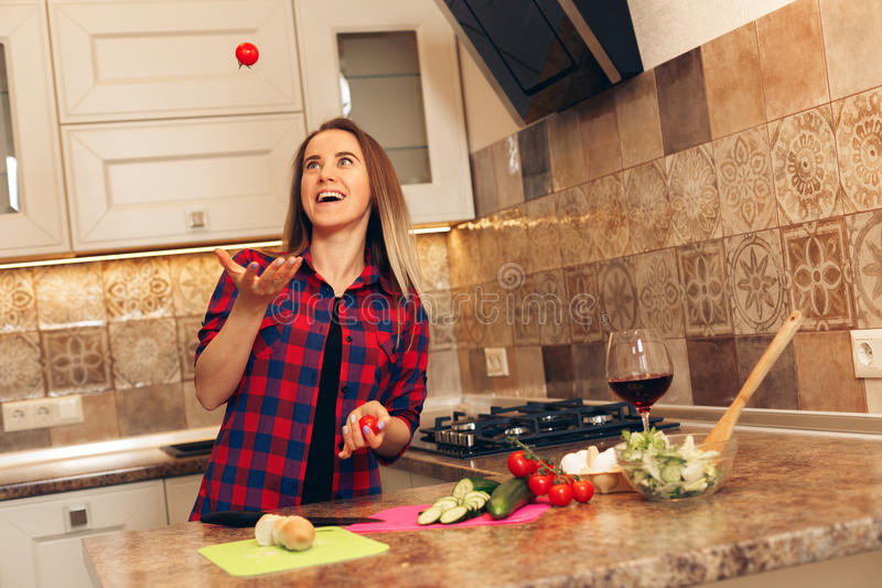 Young woman with tomatoes throwing in air. Female holding and throwing red tomato stock photo