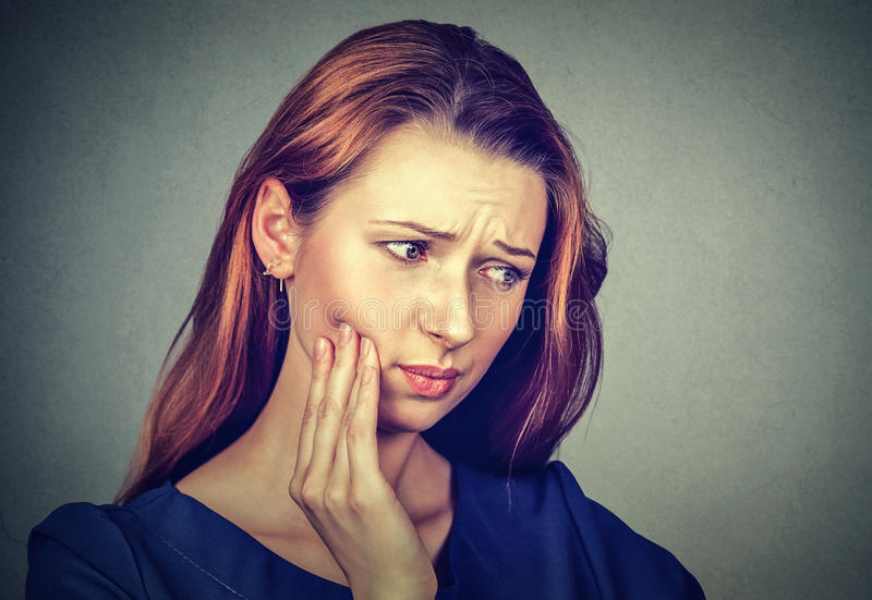 Young woman with toothache crown problem pain. Closeup portrait young woman with sensitive toothache crown problem about to cry from pain touching outside mouth stock image