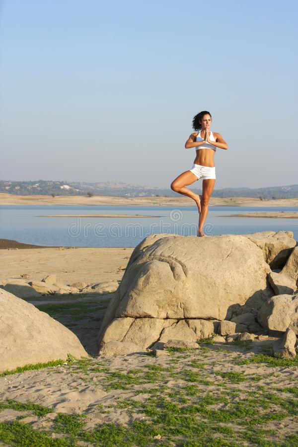 A young woman on top of a rock doing yoga royalty free stock photos