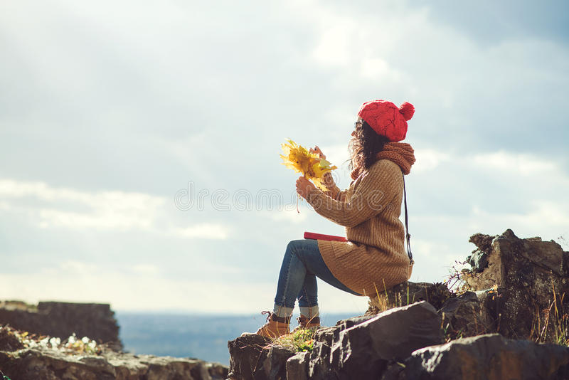 Young woman on the top of a rock enjoys the view of sunset over an autumn forest. Lifestyle and autumn concept. royalty free stock photography