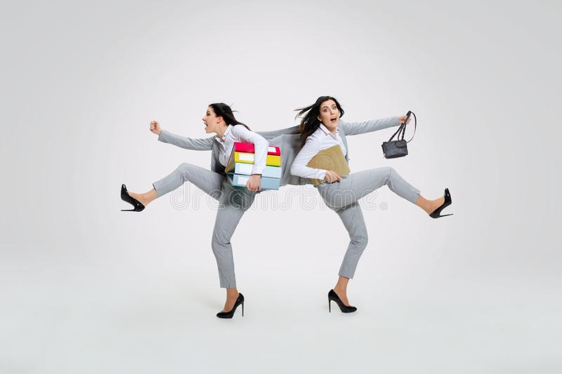 Young woman torning between cases. And trying to do everything - holding folders and laptop on the run in different directions. Concept of office worker`s stock photography