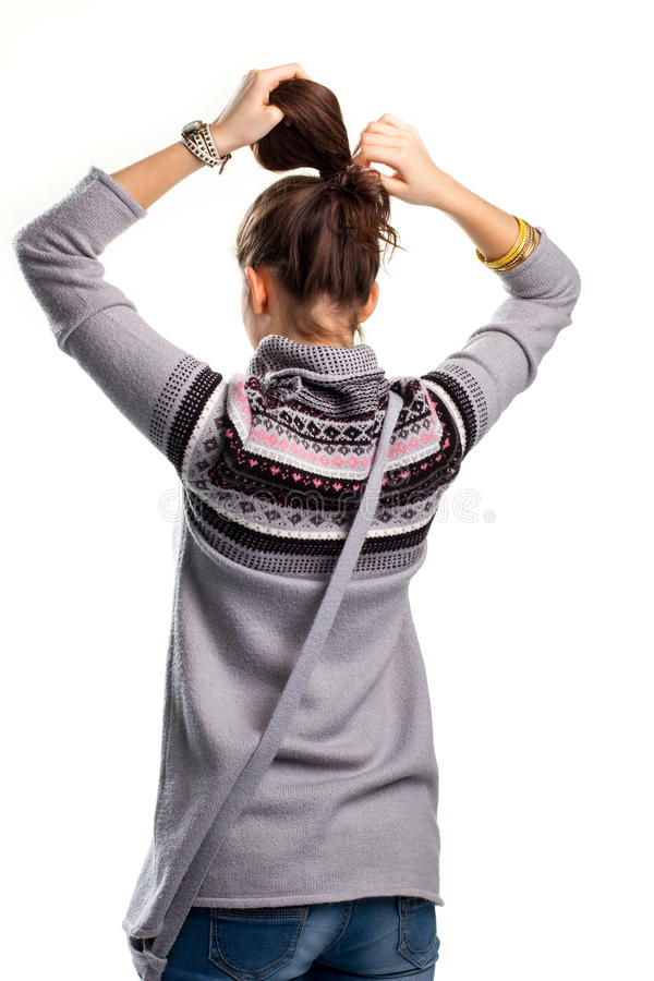 Young woman touches hair. Back view of patterned sweater. Model is tying pony tail. Example of simple hairdo stock photos