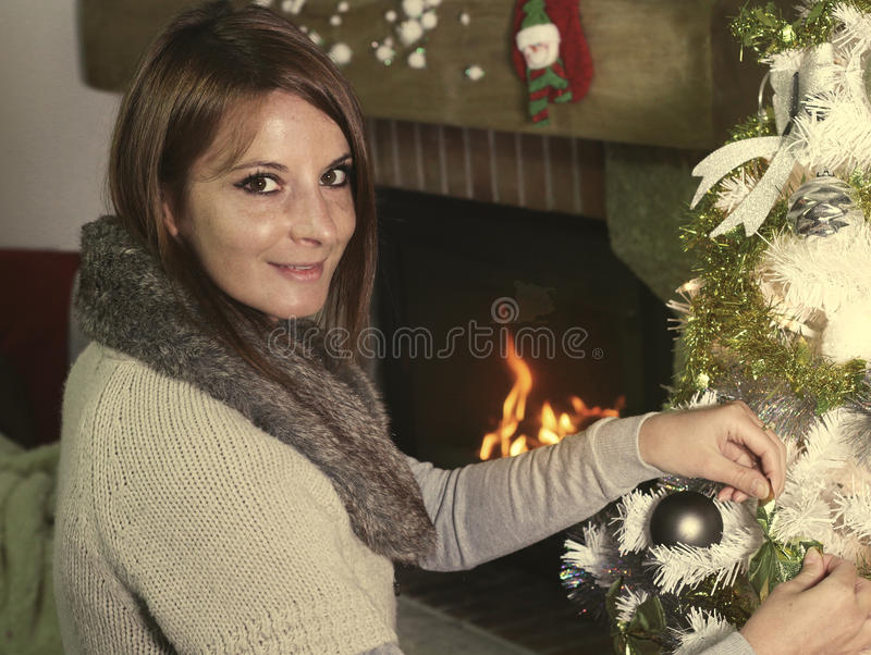 Young woman touching Christmas ornament. Young woman touching Christmas decorations in front of a fireplace royalty free stock photos