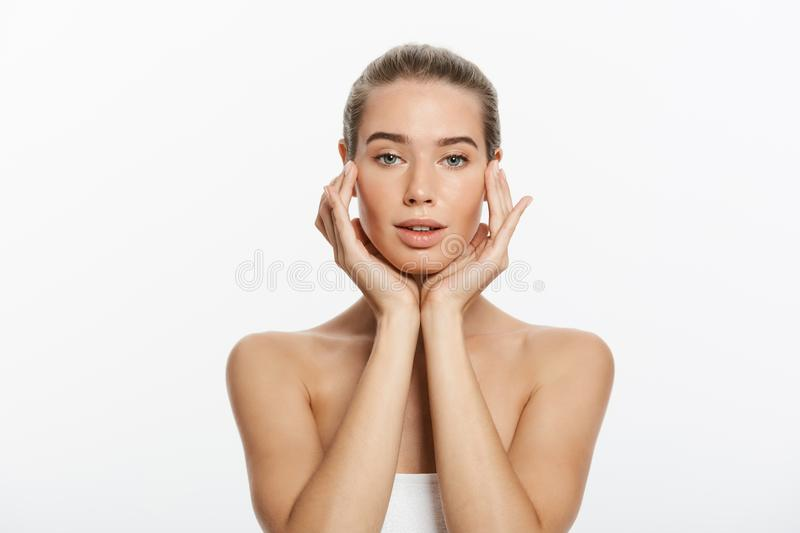 Young woman touching her face isolated on white background stock photos