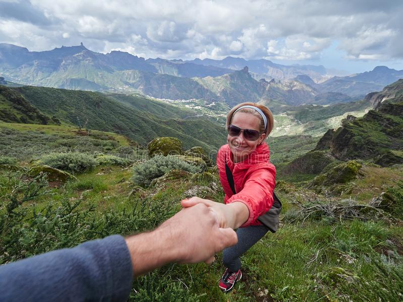 Young woman tourist in alpine zone in summer, man helping her to royalty free stock image
