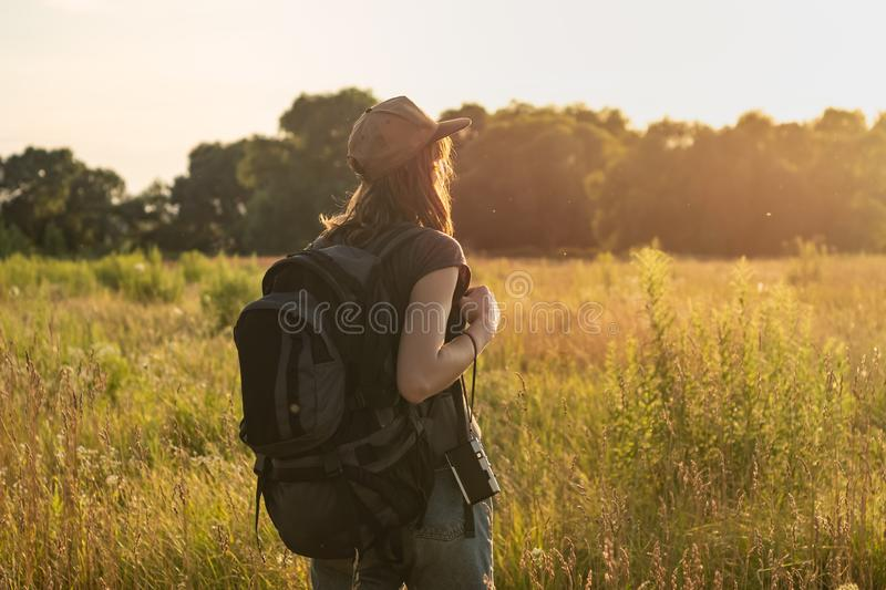 Young woman with tourist backpack in field. Female person looking at sunset in high grass of beautiful rural area in summer royalty free stock photo