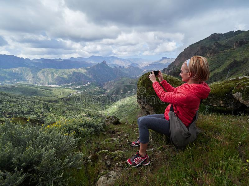 Young woman tourist with backpack sitting on cliff`s edge and ta royalty free stock images