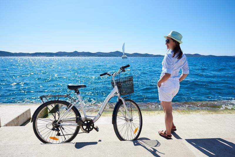 Young woman tourist biker with city bicycle in the town near the sea royalty free stock image