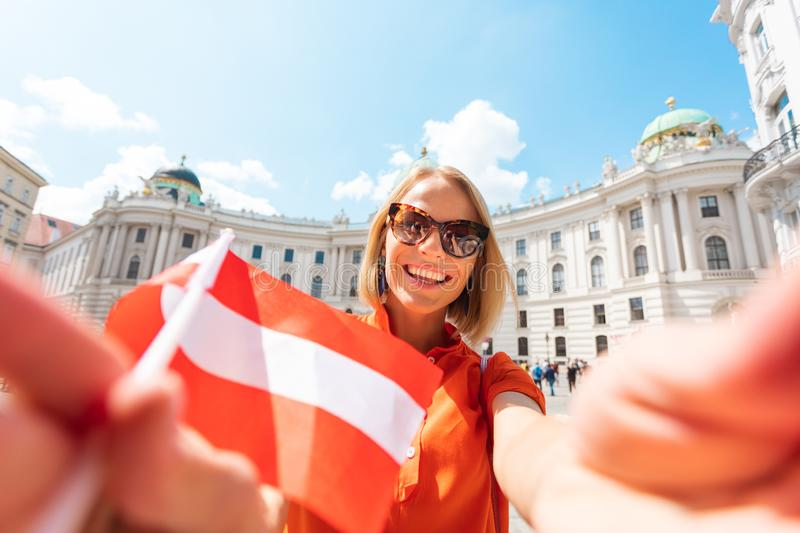 Young happy woman tourist with the flag of Austria makes selfie photo on the background of Michaelplatz and Hofburg in royalty free stock photo