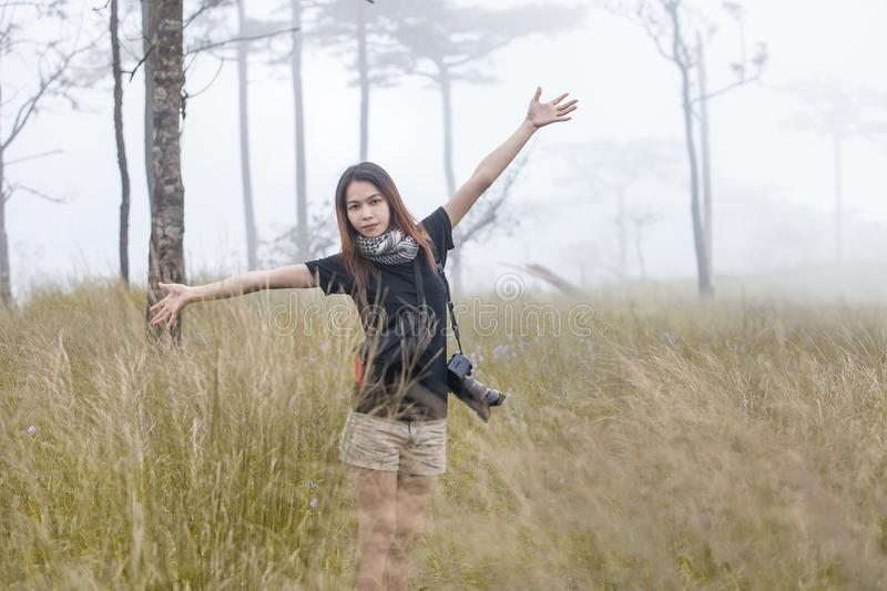 Young woman tourist with a camera walking along the trail in the rain forest. In northern Thailand royalty free stock images