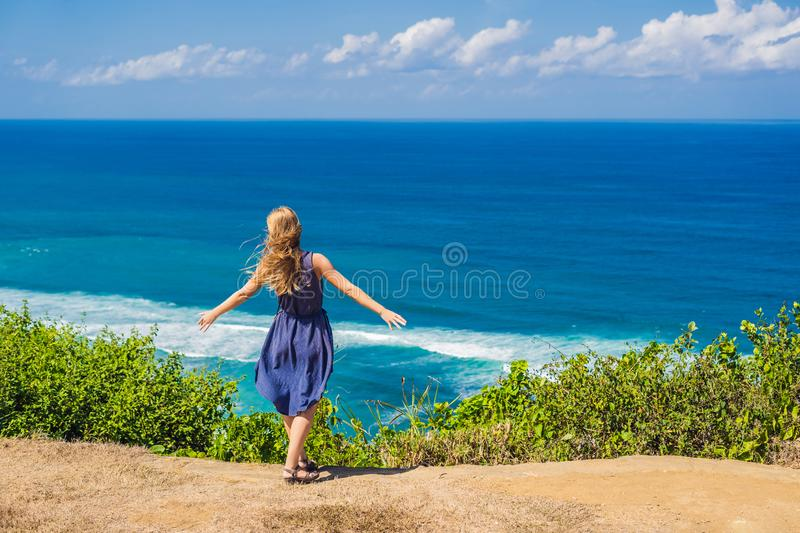 Young woman tourist on a cliff above the beach. Empty paradise b. Each, blue sea waves in Bali island, Indonesia. Suluban and Nyang Nyang place stock photography