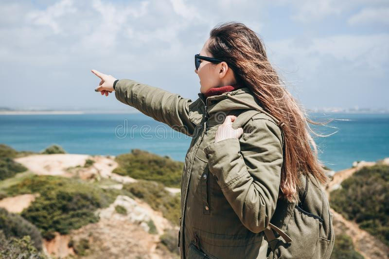 A young woman tourist enjoys beautiful views of the Atlantic Ocean and the landscape. Young woman tourist with a backpack enjoying beautiful views of the stock image