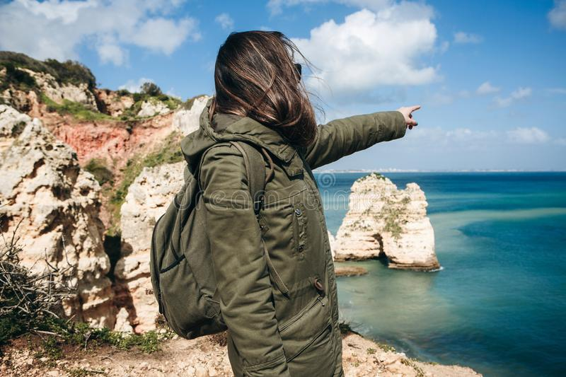 A young woman tourist enjoys beautiful views of the Atlantic Ocean and the landscape. Young woman tourist with a backpack enjoying beautiful views of the stock photography