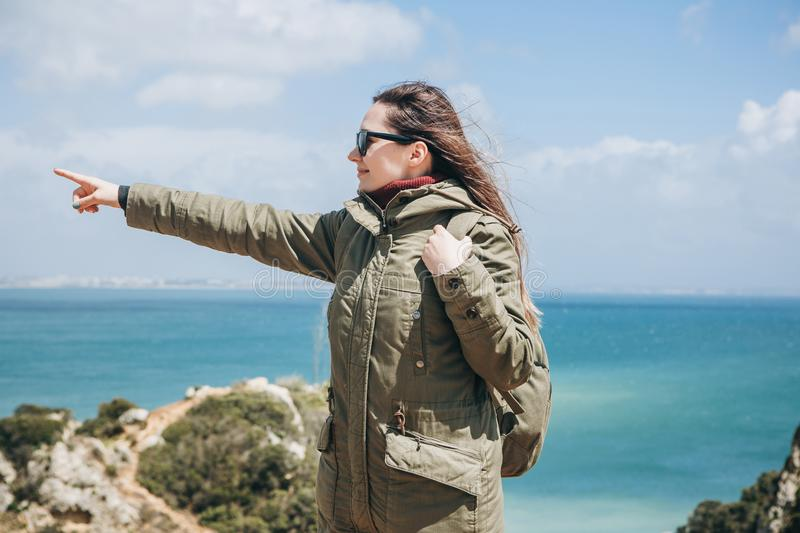 A young woman tourist enjoys beautiful views of the Atlantic Ocean and the landscape. Young woman tourist with a backpack enjoying beautiful views of the royalty free stock photo