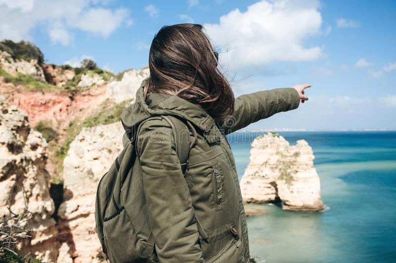 A young woman tourist enjoys beautiful views of the Atlantic Ocean and the landscape. Young woman tourist with a backpack enjoying beautiful views of the stock photos