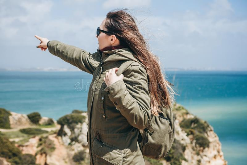 A young woman tourist enjoys beautiful views of the Atlantic Ocean and the landscape. Young woman tourist with a backpack enjoying beautiful views of the royalty free stock images