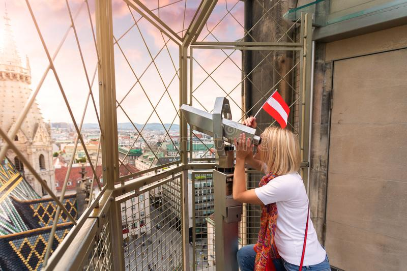 A young woman with the flag of Austria in her hands looks through observation binoculars and enjoys the panorama of the stock photography