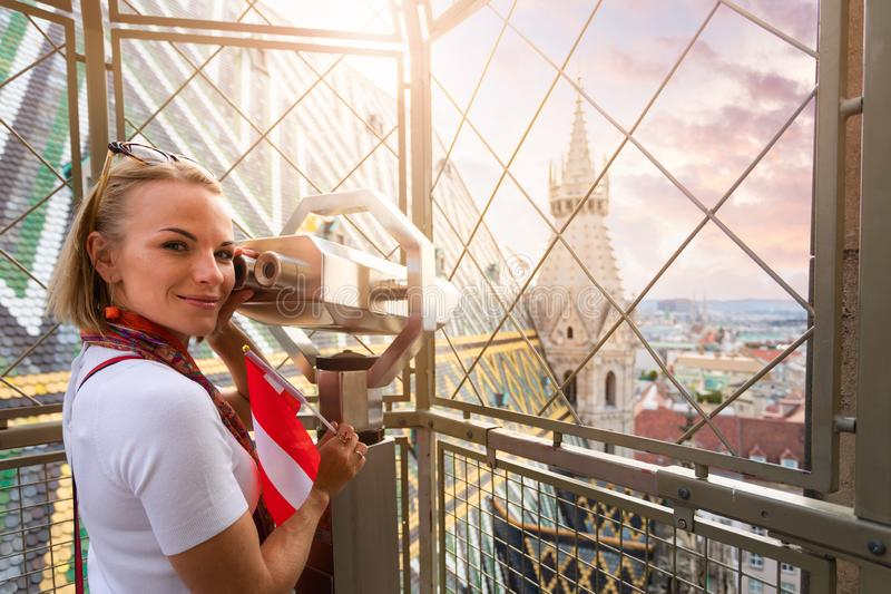 A young woman with the flag of Austria in her hands looks through observation binoculars and enjoys the panorama of the stock photos