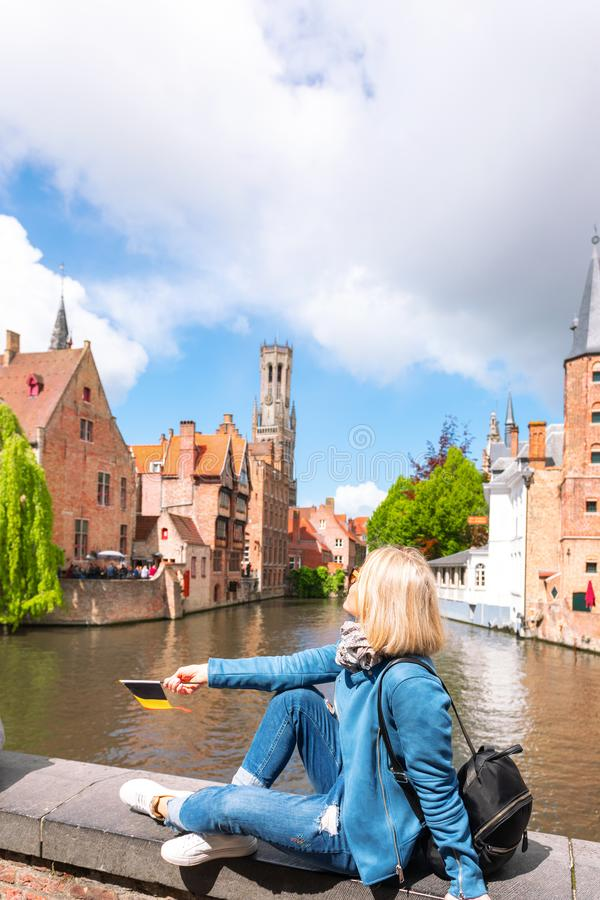 A young woman with the flag of Belgium in her hands is enjoying the view of the canals in the historical center of royalty free stock photo