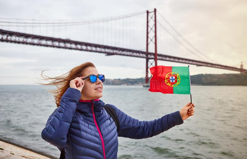 Young woman tourist holding the flag of Portugal in hands and enjoying landscape view on the famous iron bridge 25th of April stock photos