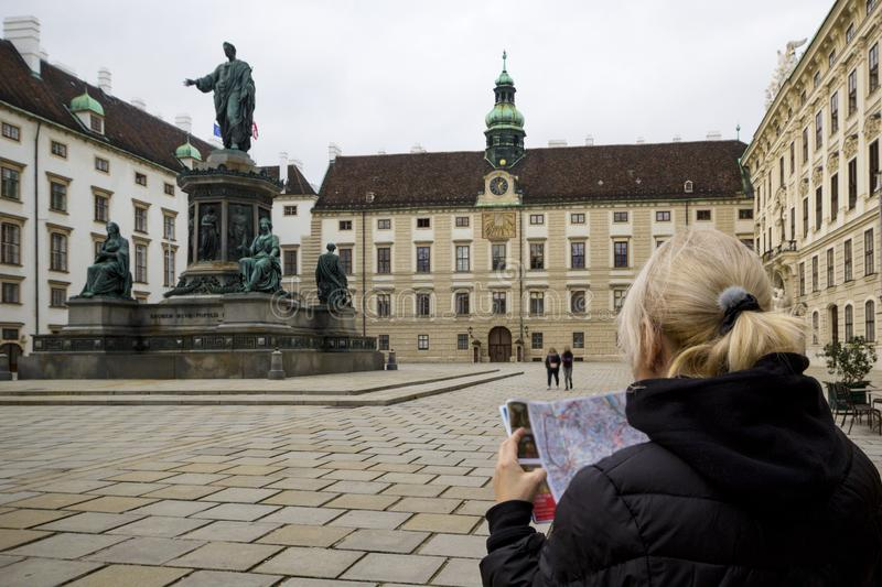 Young woman tourist looking at map, girl visit in  Vienna Hofburg Imperial Palace at courtyard with monument Kaiser Franz I,. Vienna, Austria stock images