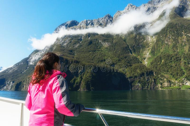 Woman Tourist on Ship Deck in Milford Sound. Young woman tourist looks at fjord scenery from the ship deck in Milford Sound in Fiordland National Park, South stock photo