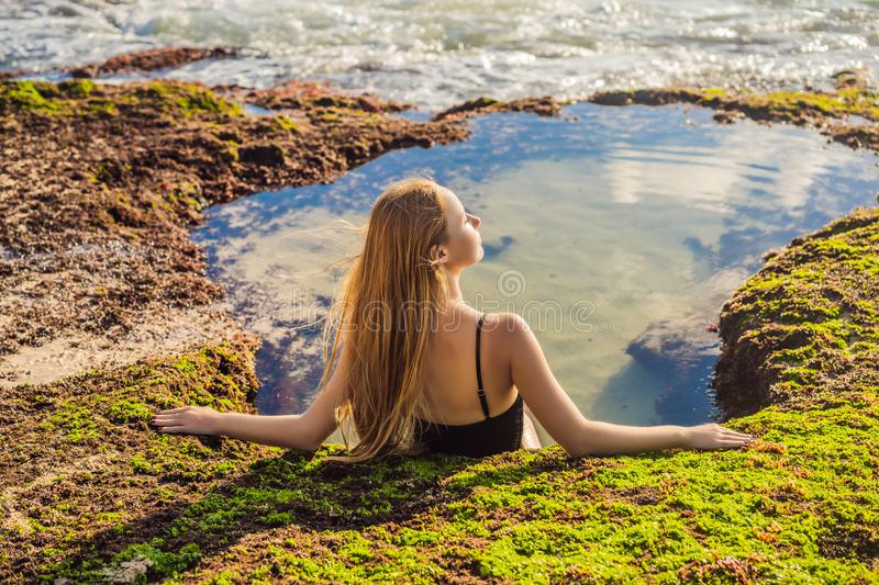 Young woman tourist on Pantai Tegal Wangi Beach sitting in a bath of sea water, Bali Island, Indonesia. Bali Travel. Concept stock images