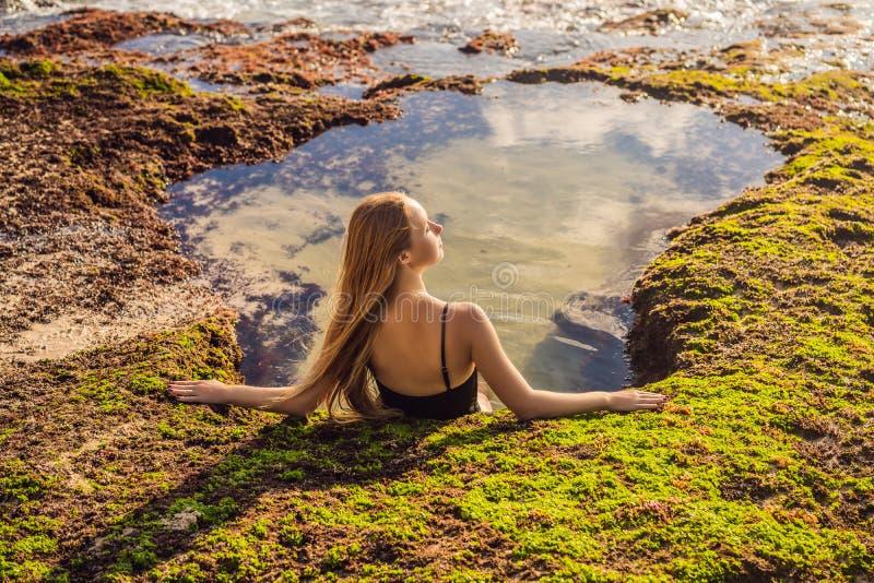 Young woman tourist on Pantai Tegal Wangi Beach sitting in a bath of sea water, Bali Island, Indonesia. Bali Travel. Concept stock photography