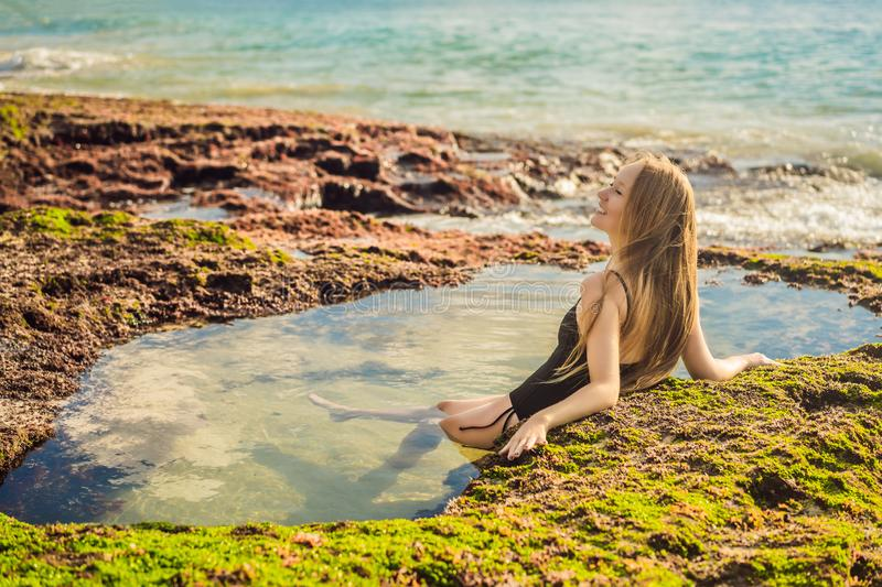 Young woman tourist on Pantai Tegal Wangi Beach sitting in a bath of sea water, Bali Island, Indonesia. Bali Travel. Concept royalty free stock images