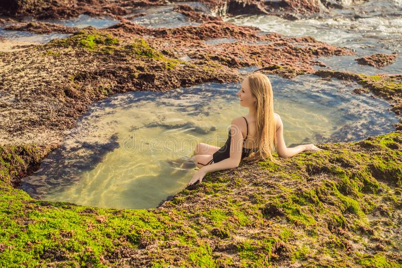 Young woman tourist on Pantai Tegal Wangi Beach sitting in a bath of sea water, Bali Island, Indonesia. Bali Travel. Concept royalty free stock photo