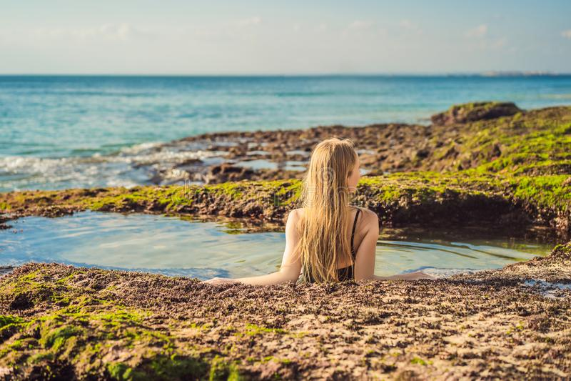 Young woman tourist on Pantai Tegal Wangi Beach sitting in a bath of sea water, Bali Island, Indonesia. Bali Travel. Concept stock photo