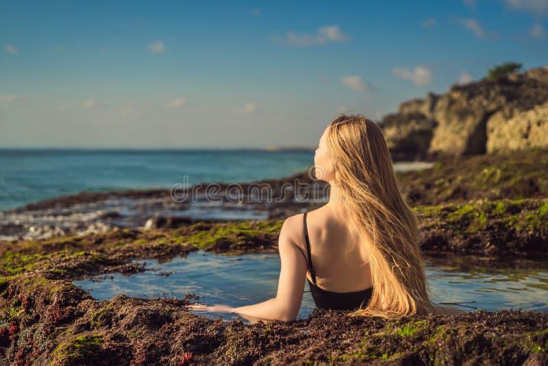 Young woman tourist on Pantai Tegal Wangi Beach sitting in a bath of sea water, Bali Island, Indonesia. Bali Travel. Concept royalty free stock photos