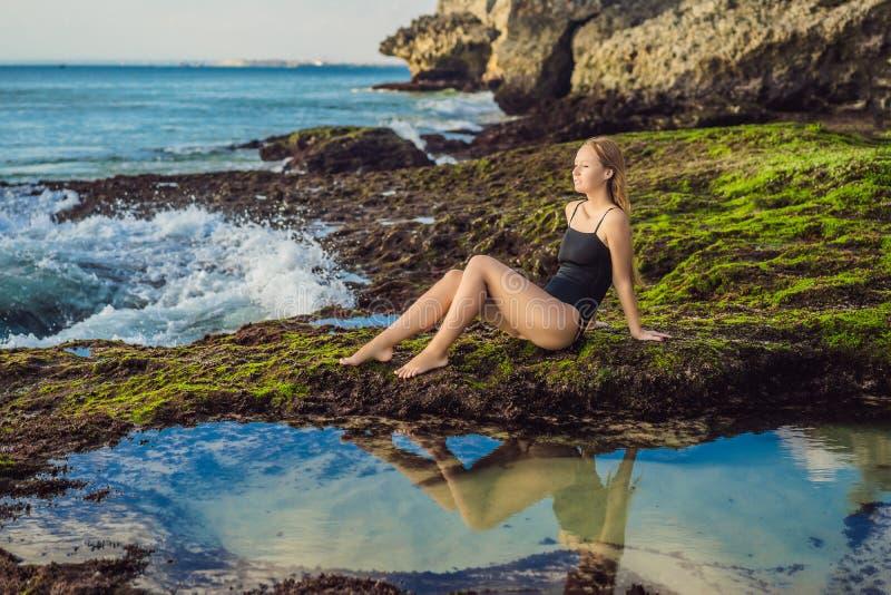 Young woman tourist on Pantai Tegal Wangi Beach sitting in a bath of sea water, Bali Island, Indonesia. Bali Travel. Concept royalty free stock image