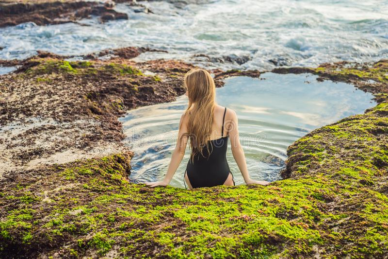 Young woman tourist on Pantai Tegal Wangi Beach sitting in a bath of sea water, Bali Island, Indonesia. Bali Travel. Concept royalty free stock photography