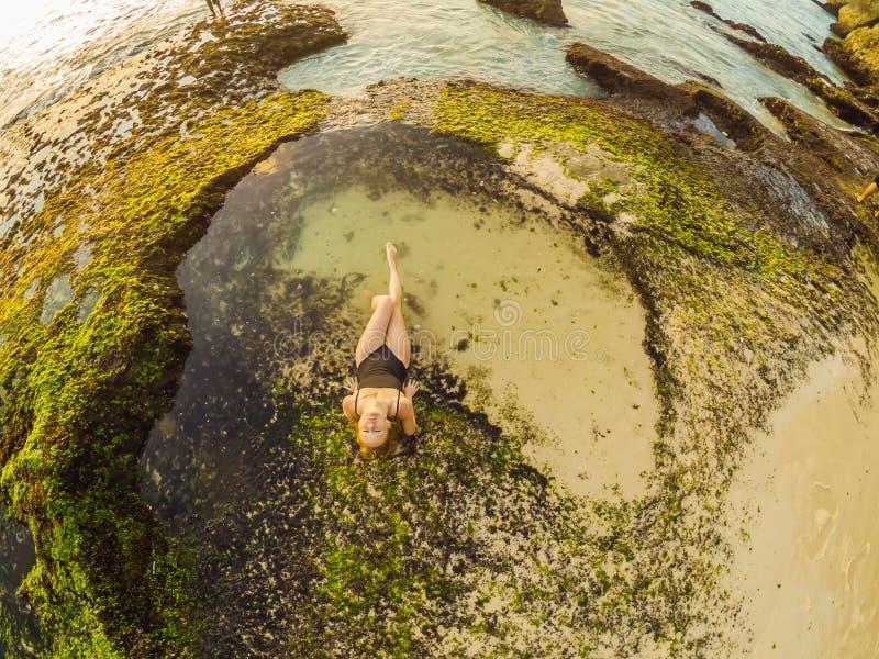 Young woman tourist on Pantai Tegal Wangi Beach sitting in a bath of sea water, Bali Island, Indonesia. Bali Travel. Concept stock photos