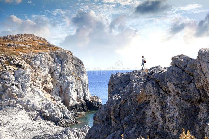 Young woman tourist is standing on a high cliff overlooking the royalty free stock images