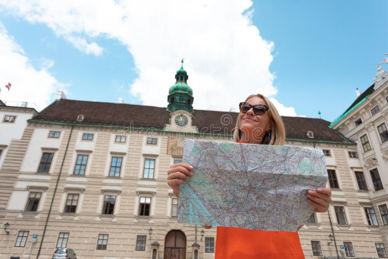 Young woman tourist stands with a city map on the background of the Hofburg courtyard in Vienna, Austria stock photo