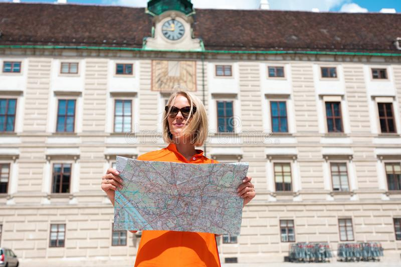 Young woman tourist stands with a city map on the background of the Hofburg courtyard in Vienna, Austria stock image