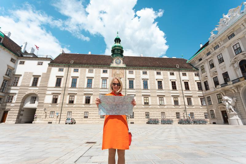 Young woman tourist stands with a city map on the background of the Hofburg courtyard in Vienna, Austria royalty free stock photo
