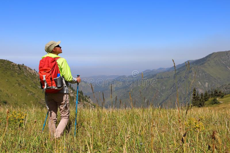 Young woman tourist stands in the middle of a meadow royalty free stock photo
