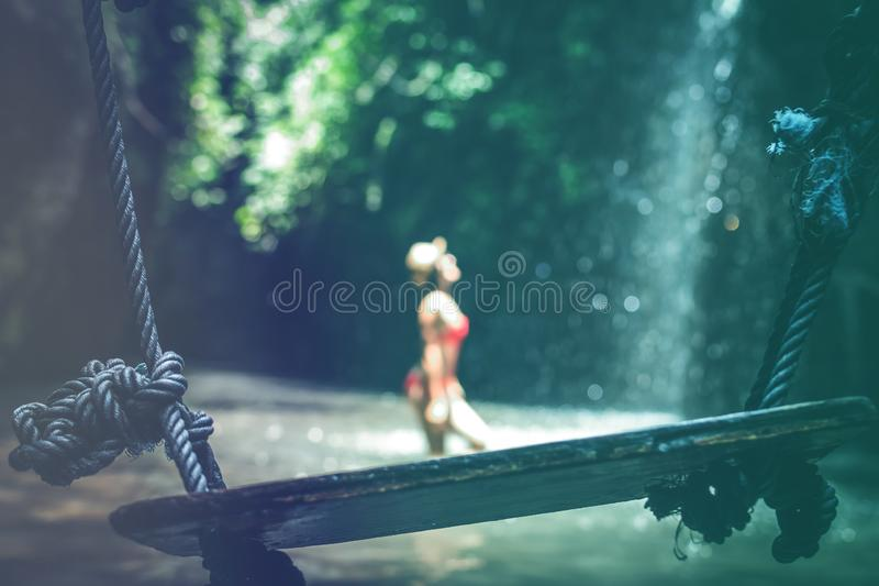 Young woman tourist with straw hat deep in the rainforest with waterfall background. Bali island. Indonesia royalty free stock image