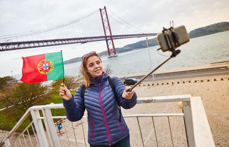 Young woman tourist take selfies on the background of famous iron 25th of April bridge and holding the flag of Portugal in hands stock photo
