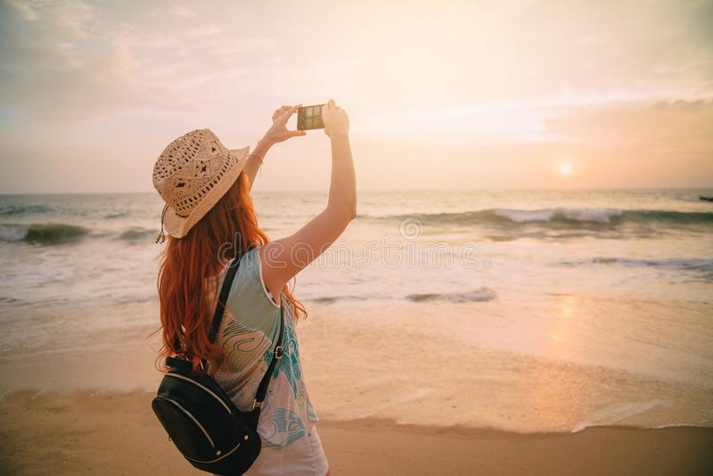Young woman uses a smartphone on the beach at sunset stock image