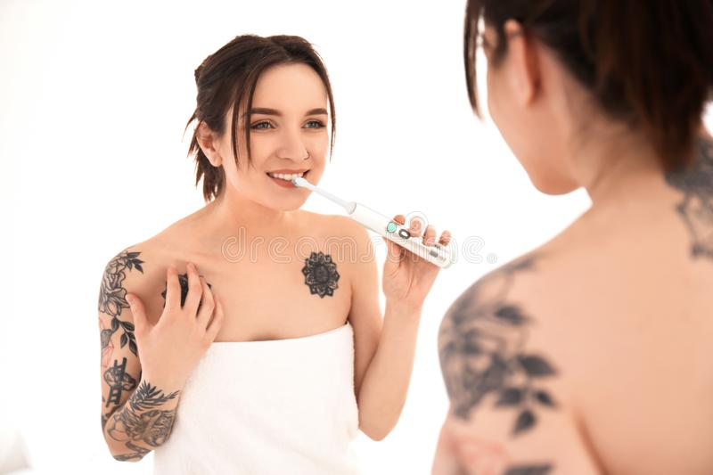 Young woman in towel brushing teeth near mirror at home. Morning routine stock photos