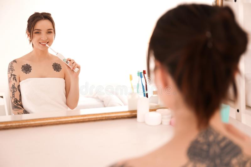 Young woman in towel brushing teeth near mirror at home. Morning routine stock images