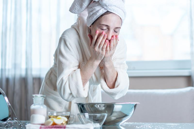 Young woman with a towel on head washing face with water in the morning. Concept of hygiene and care for the skin stock photography