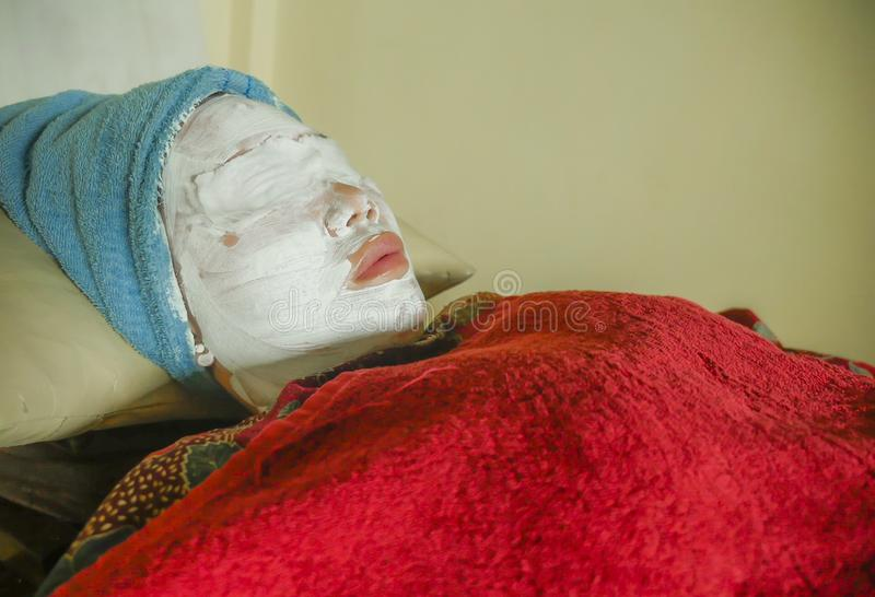 Young woman with towel wrapped on head and face mask lying on bed at wellness spa receiving beauty facial treatment in well being. Skin care and healthy royalty free stock images