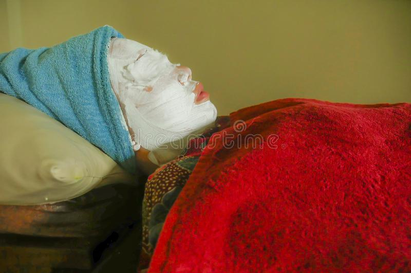 Young woman with towel wrapped on head and face mask lying on bed at wellness spa receiving beauty facial treatment in well being. Skin care and healthy stock photos